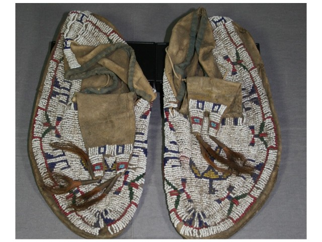 Iroquois beaded leather moccasins before conservation treatment and stabilization repair and display for museum collection by spicer Art Conservation, experts in the conservation of Native American object, paper, textile artifacts