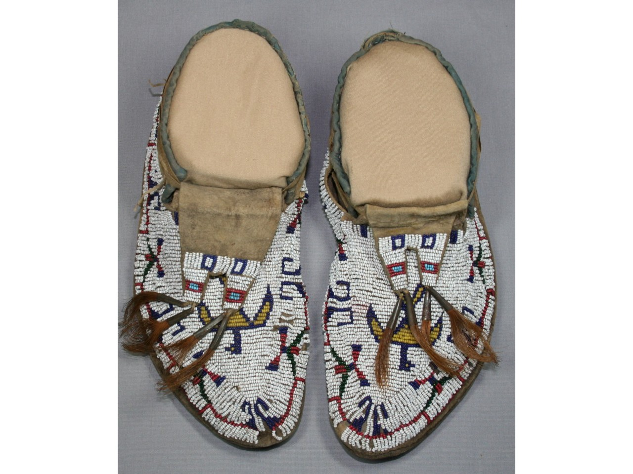 Iroquois beaded leather moccasins after conservation preservation treatment and stabilization repair and display for museum collection by spicer Art Conservation, experts in the conservation of Native American object, paper, textile artifacts