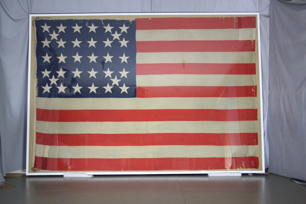 After conservation of historic civil war battle flag, pressure mount of textile, flag repair, conservation, preservation,